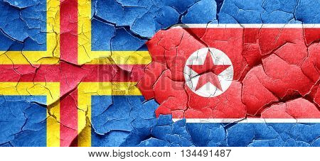 aland islands with North Korea flag on a grunge cracked wall