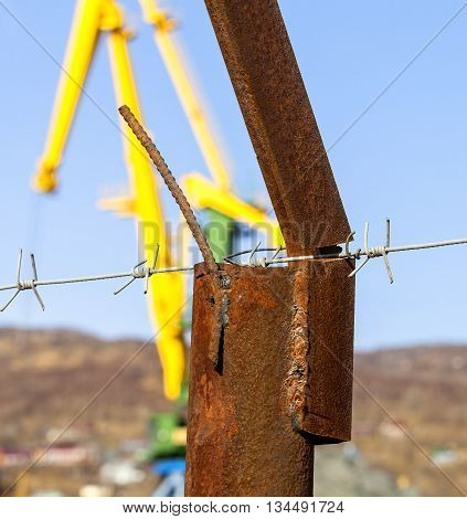 barbed wire on the rusty post against the blue sky and cranes