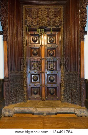 Chettinad India - October 17 2013: Chidambara Palace in Kadiapatti. Massive wooden dark brown antique door set in frame of hand chiseled wood. Mango leaves have spiritual and healing powers.