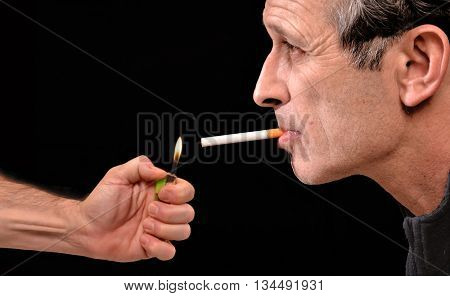 Hand lighting a smoker man cigarette on black background.