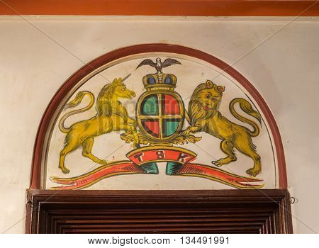 Chettinad India - October 17 2013: Chidambara Palace in Kadiapatti. Wall painting above door showing United Kingdom coat of arms.
