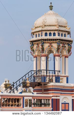 Chettinad India - October 17 2013: Chidambara Palace in Kadiapatti. View on lookout tower against blue sky. Combination of colors as decoration.