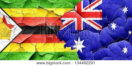 Zimbabwe flag with Australia flag on a grunge cracked wall