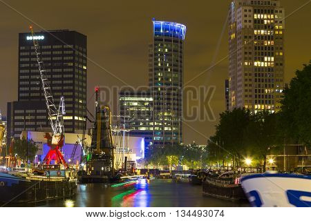 Rotterdam, Netherlands - 24 MAY 2015: Illuminated old cranes and modern office buildings at night in historical harbor of Rotterdam Netherlands