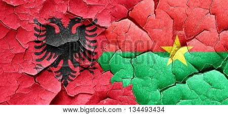 Albania flag with Burkina Faso flag on a grunge cracked wall