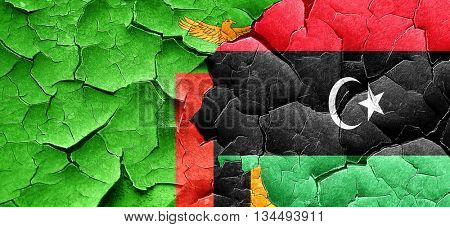 Zambia flag with Libya flag on a grunge cracked wall