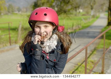 pretty preteen with roller skate helmet eat a cake