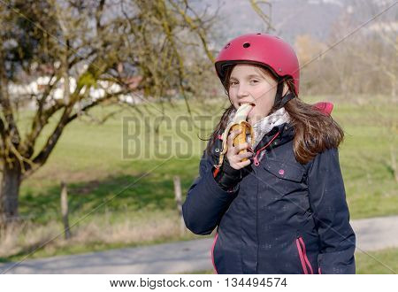 pretty preteen with roller skate helmet eat a banana