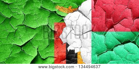 Zambia flag with Madagascar flag on a grunge cracked wall