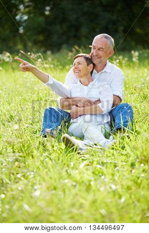 Senior couple sitting in grass in nature and woman pointing into the distance