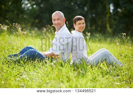 Relaxed senior couple sitting in nature in summer