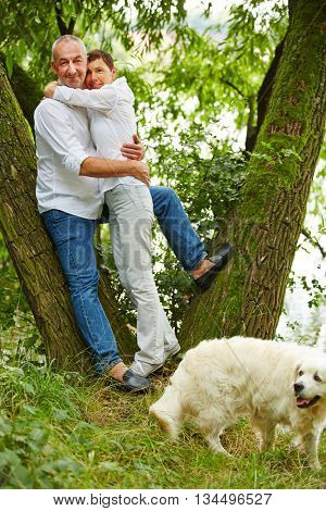 Senior couple taking dog for walk in nature in summer