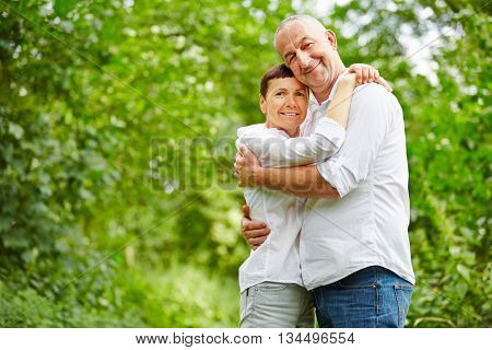 Happy senior couple embracing in a forest in summer