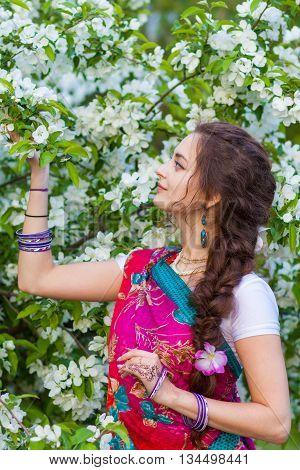 Asian woman wearing traditional sari with mehndi near apple tree