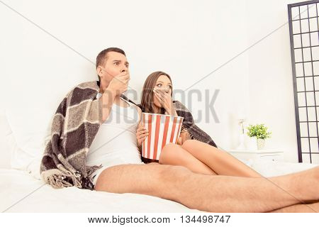 Scared Young Beautiful Couple At Home Watching A Movie And Eating Popcorn