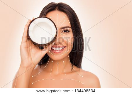 Closeup Photo Of Cheerful Pretty Young Woman Holdind Coconut Near Her Face With Arrows