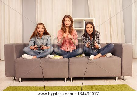 Pretty girl sitting on couch and waiting while her sisters playing video games