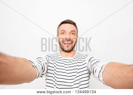 Attractive cheerful happy man making selfie and smiling