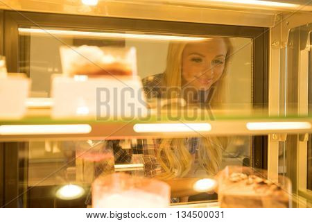 A beautiful young woman ordering from a nice girl at the bar in a coffee shop