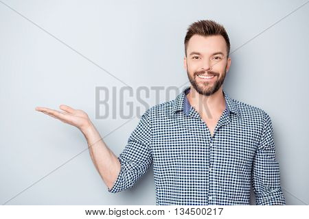 Young Happy Smiling Businessman Demonstrating His Product