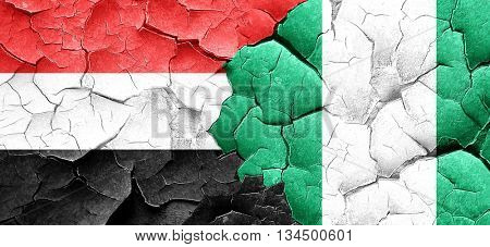 Yemen flag with Nigeria flag on a grunge cracked wall
