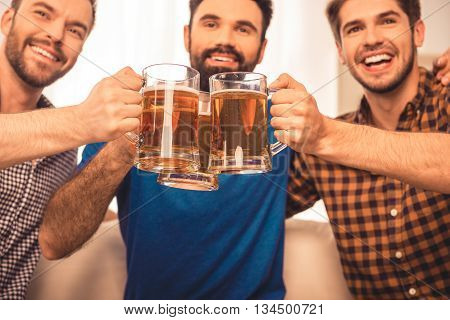 Cheers! Close Up Photo Of Handsome Men Celebrating  And Clinking Glass Of Beer