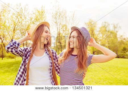 Two Happy Laughing Sisters Having Walk In The Park