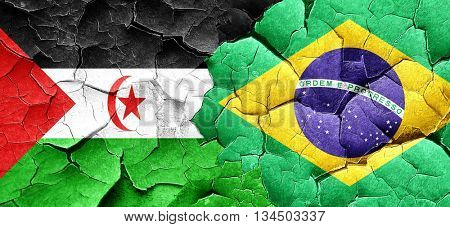 Western sahara flag with Brazil flag on a grunge cracked wall