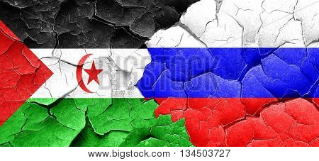 Western sahara flag with Russia flag on a grunge cracked wall