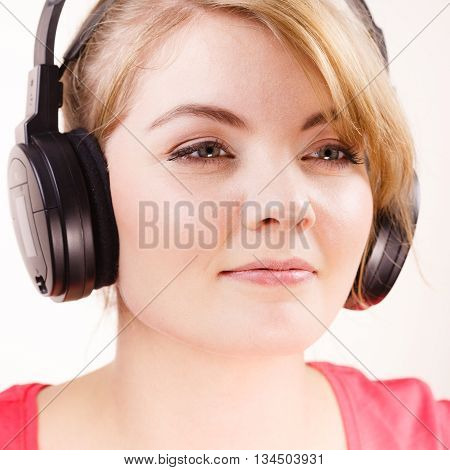 Woman face big headphones listening music mp3. Smiling female model. People leisure happiness concept.