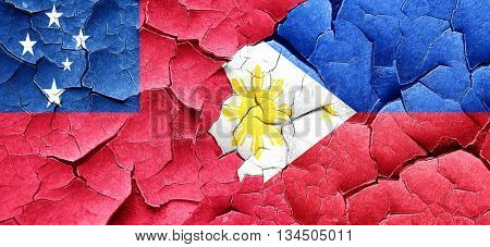 Samoa flag with Philippines flag on a grunge cracked wall