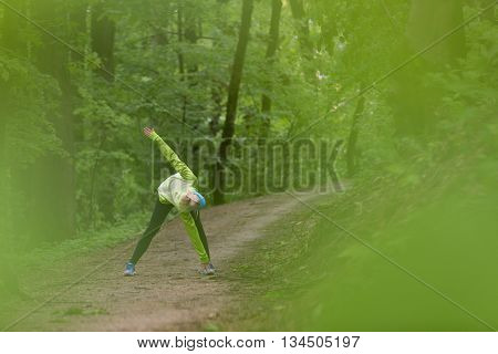 Sporty young female working out in forest.  Female runner during outdoor workout in nature. Fitness model outdoors. Weight Loss. Healthy lifestyle.