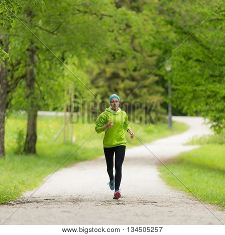 Sporty young female runner in city park.  Running woman. Female runner during outdoor workout in nature. Fitness model outdoors. Weight Loss. Healthy lifestyle.