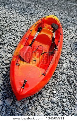 red kayak with oarson on sea shore pebbles