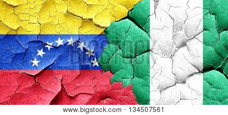Venezuela flag with Nigeria flag on a grunge cracked wall