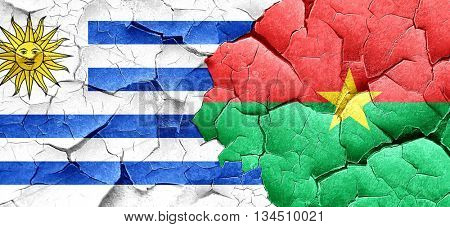 Uruguay flag with Burkina Faso flag on a grunge cracked wall