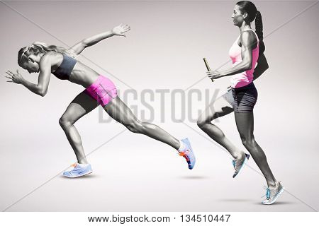 Sporty woman running on a grey background