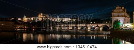 Panorama of Prague with Vltava river in the foreground, Charles Bridge on right and St. Vitus Cathedral on the horizon. Night  city skyline
