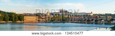 Panorama of Prague with Vltava river in the foreground, Charles Bridge on right and St.   Vitus Cathedral on the horizon. City Panorama at sunrise on a summer day
