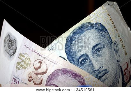 Some Singaporean dollars with a dark background.