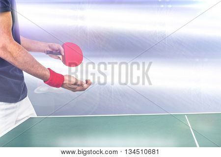 Mid section of athlete man playing table tennis against spotlights