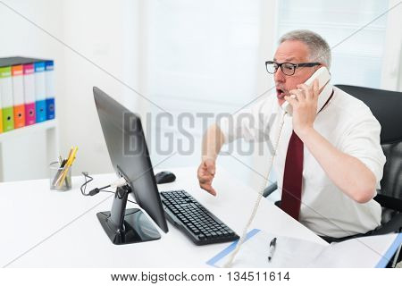 Portrait of an angry businessman yelling at the phone