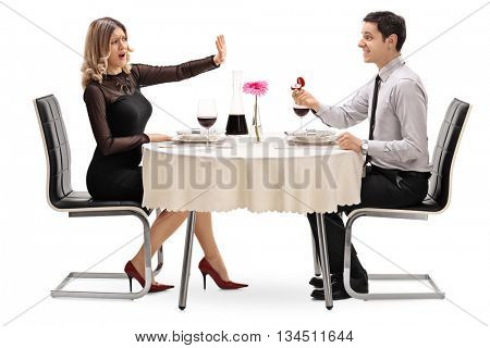 Woman trying to stop her boyfriend from proposing seated on a romantic date isolated on white background