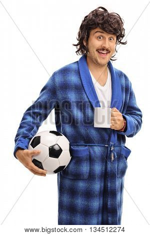 Vertical shot of a young man in a bathrobe holding a football and a coffee cup isolated on white background