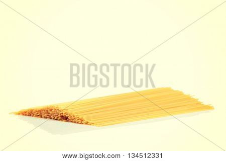 Uncooked dry fettuccine pasta isolated on a white background