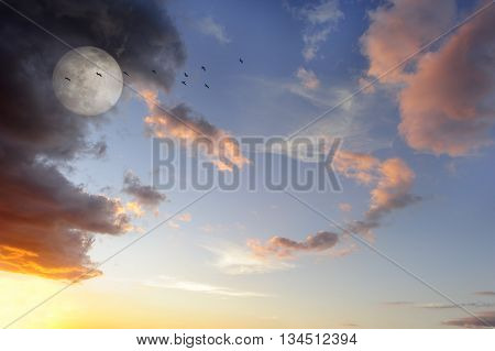 Moon clouds birds is a vibrant surreal fantasy like cloudscape with the ethereal heavenly full moon rising among the vibrant wispy colorful cloudscape.