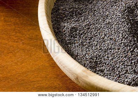 Poppy seeds in a wooden bowl on a wooden background