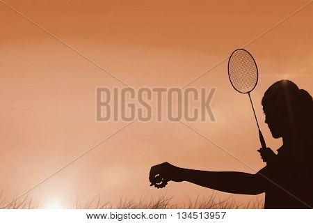 Female athlete holding a badminton racquet ready to serve against sun rising