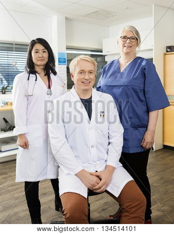 Confident Male Doctor Sitting By Team In Clinic