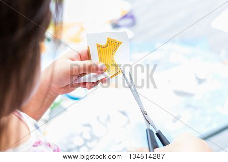 Little Girl Is Cutting The Paper